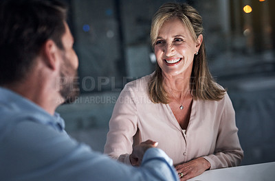 Buy stock photo Shot of two businesspeople shaking hands in an office at night