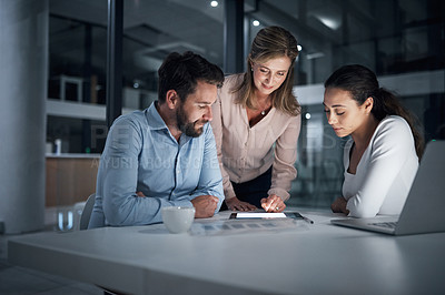 Buy stock photo Shot of a group of businesspeople using a digital tablet together in an office at night