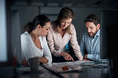 Buy stock photo Shot of a group of businesspeople going through paperwork together in an office at night