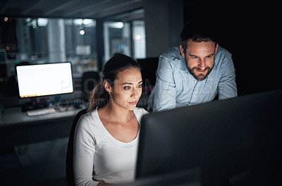 Buy stock photo Shot of two businesspeople using a computer together in an office at night