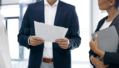 Buy stock photo Closeup shot of a group of businesspeople going through paperwork together in an office