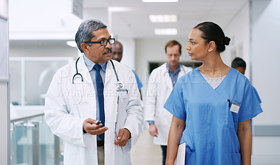 Buy stock photo Shot of medical practitioners talking while walking through a hospital corridor