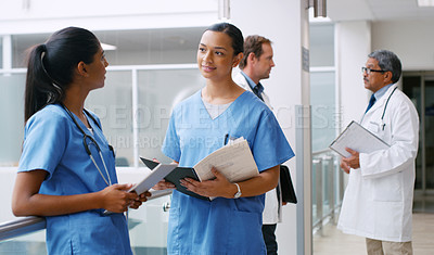 Buy stock photo Shot of two nurses having a discussion in a hospital corridor