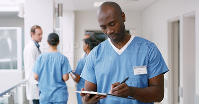 Buy stock photo Shot of a medical practitioner writing on a clipboard in a hospital corridor