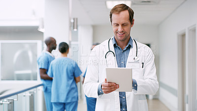 Buy stock photo Shot of a mature doctor using a digital tablet in a hospital corridor