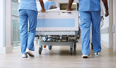 Buy stock photo Closeup shot of a group of medical practitioners pushing a patient down a hospital corridor in a gurney