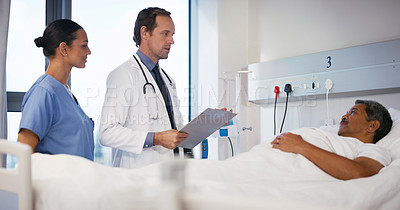 Buy stock photo Shot of a doctor and a nurse talking to a patient lying in a hospital bed