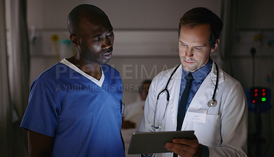 Buy stock photo Shot of two medical practitioners using a digital tablet together in a hospital ward