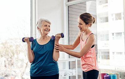 Buy stock photo Shot of a fitness instructor helping a senior woman with some weightlifting exercises
