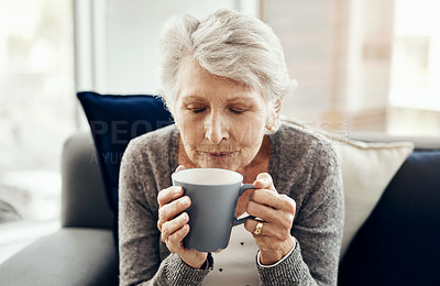 Buy stock photo Shot of a senior woman enjoying a cup of coffee while relaxing at home