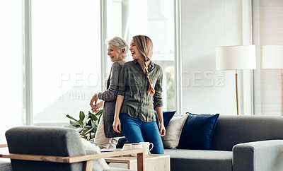Buy stock photo Shot of a senior woman and her adult daughter dancing together at home
