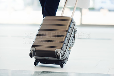 Buy stock photo Rearview shot of an unrecognizable businesswperson pulling a suitcase while walking through an airport terminal during the day