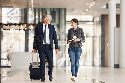 Buy stock photo Full length shot of two happy businesspeople walking through an airport terminal together during the day