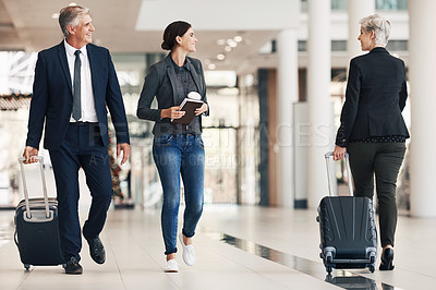 Buy stock photo Full length shot of a group of businesspeople walking through an airport terminal before travelling during the day