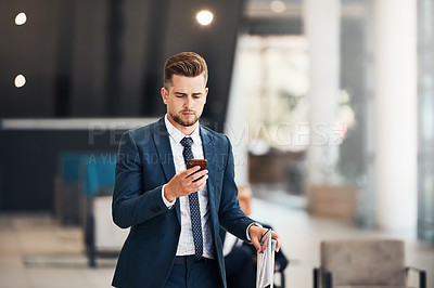 Buy stock photo Cropped shot of a handsome young businessman using a cellphone while standing in an airport terminal during the day