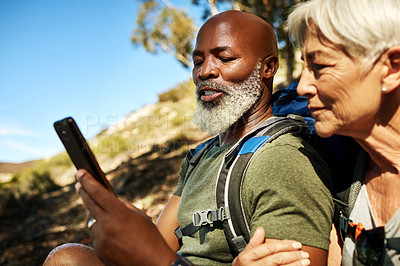 Buy stock photo Shot of a senior couple using a cellphone together while hiking out in the mountains