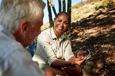 Buy stock photo Shot of a senior couple sitting down and using a cellphone together while exploring out in the mountains