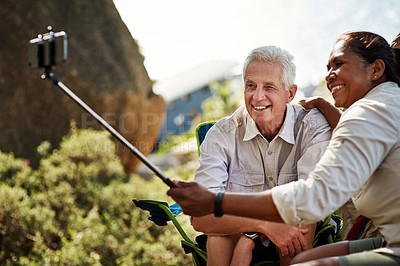 Buy stock photo Shot of a senior couple taking selfies together with a cellphone  while exploring out in the mountains