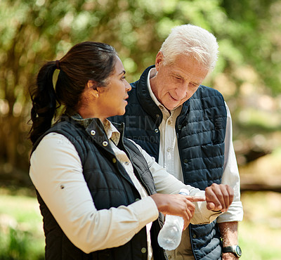 Buy stock photo Shot of a senior couple looking at the time while hiking out in the mountains