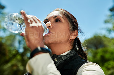 Buy stock photo Shot of a senior woman drinking water from a bottle while hiking out in the mountains