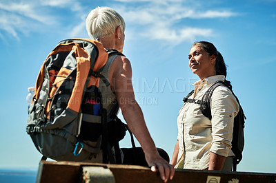 Buy stock photo Shot of two senior woman having a conversation while hiking together outdoors