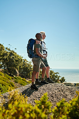 Buy stock photo Full length shot of two senior men standing on a rock and looking at the view while hiking together outdoors