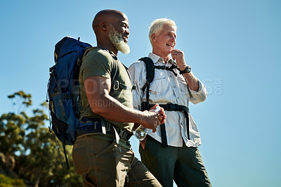 Buy stock photo Shot of two senior man standing on a rock and looking at the view while hiking together outdoors