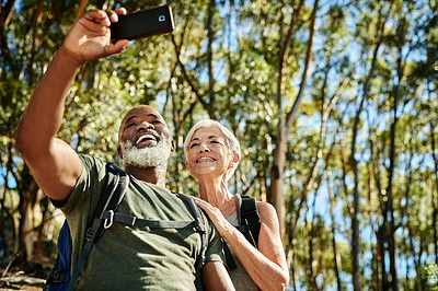 Buy stock photo Shot of a senior couple taking a selfie with a cellphone while hiking together out in the mountains
