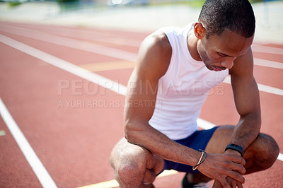 Buy stock photo Shot of a male sprinter checking his time while practicing on the track