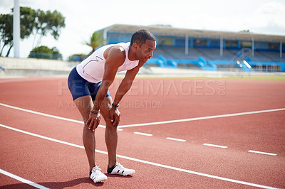Buy stock photo Shot of a male sprinter taking a break while practicing on the track