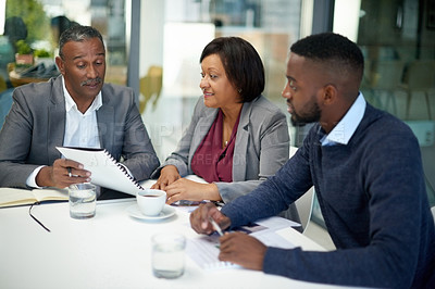 Buy stock photo Shot of corporate businesspeople going over some paperwork together inside an office