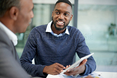 Buy stock photo Shot of two corporate businessmen using a digital tablet together inside an office