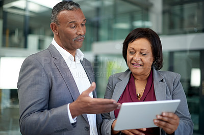 Buy stock photo Shot of two mature businesspeople using a digital tablet together inside an office