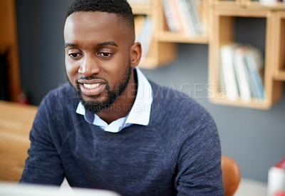 Buy stock photo Shot of a handsome young businessman working in his office