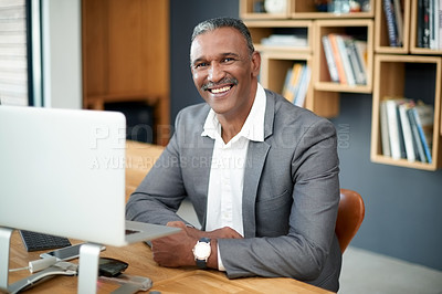 Buy stock photo Portrait of a handsome mature businessman working on a computer in his office