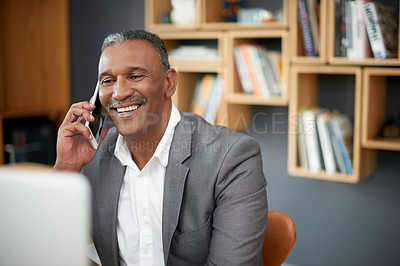 Buy stock photo Shot of a handsome mature businessman making a phone call in his office