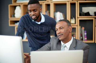 Buy stock photo Shot of two businessmen working on a computer together at work