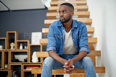 Buy stock photo Shot of a handsome young man looking thoughtful while sitting on a staircase at home