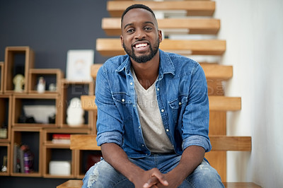 Buy stock photo Portrait of a handsome young man sitting on a staircase at home
