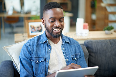 Buy stock photo Shot of a young man using a digital tablet while relaxing at home