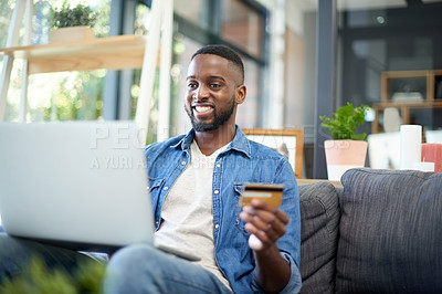 Buy stock photo Shot of a young man using a laptop and credit card at home