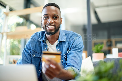 Buy stock photo Portrait of a young man using a laptop and credit card at home
