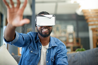 Buy stock photo Shot of a young man using a virtual reality headset at home