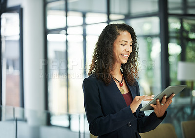 Buy stock photo Cropped shot of an attractive young businesswoman standing and using a tablet while in the office during the day