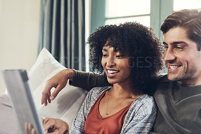 Buy stock photo Shot of an affectionate young couple using a digital tablet together while spending some quality time together at home