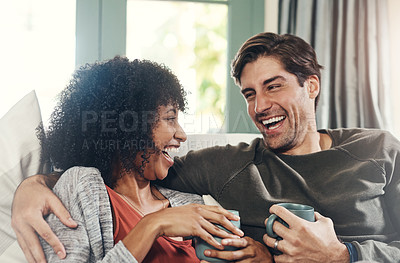 Buy stock photo Shot of an affectionate young couple drinking coffee and spending quality time together at home