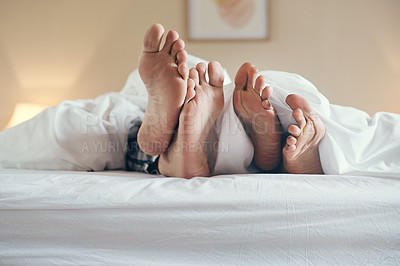 Buy stock photo Shot of an unrecognizable couple's feet poking out under the sheets while lying in bed together at home