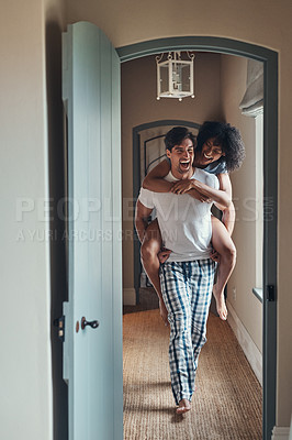 Buy stock photo Full length shot of a young man carrying his girlfriend piggy back while spending some time together at home