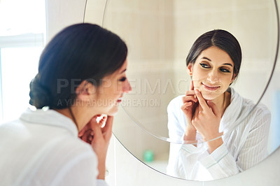 Buy stock photo Cropped shot of an attractive young woman squeezing a pimple on her face