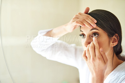 Buy stock photo Cropped shot of an attractive young woman putting in contact lenses